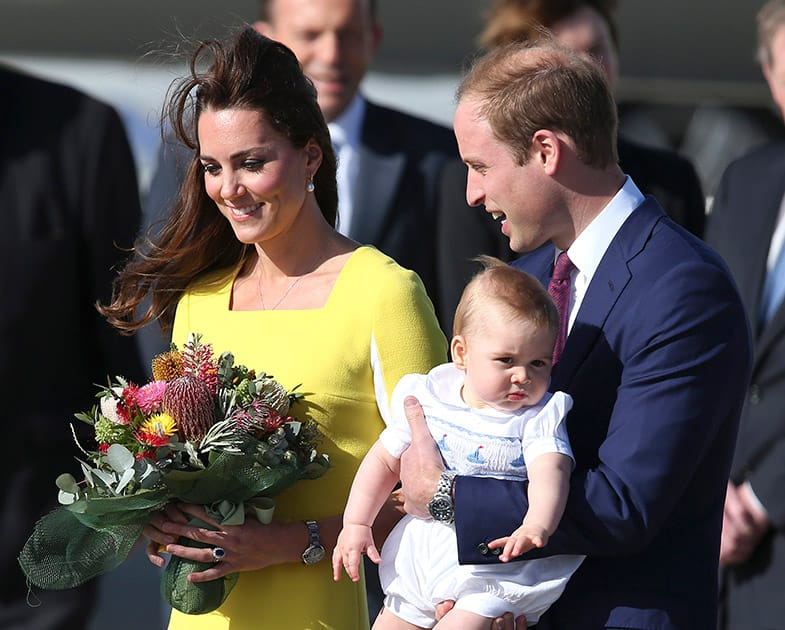 Britain`s Prince William holding his son Prince George and his wife Kate, Duchess of Cambridge, arrive in Sydney.