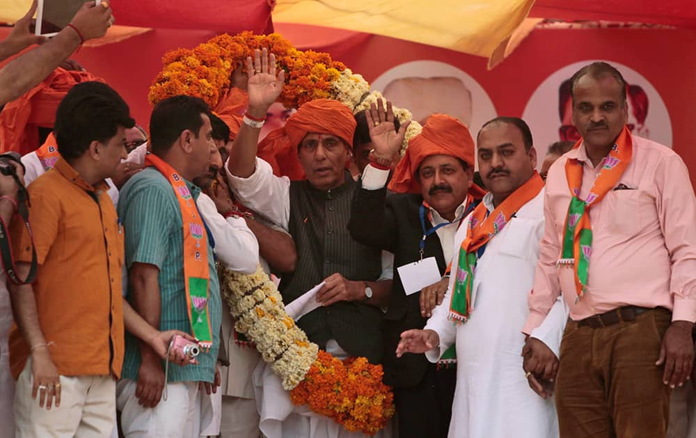 Supporters place a garland on President of Bharatiya Janata Party Rajnath Singh during an election campaign in Udhampur.