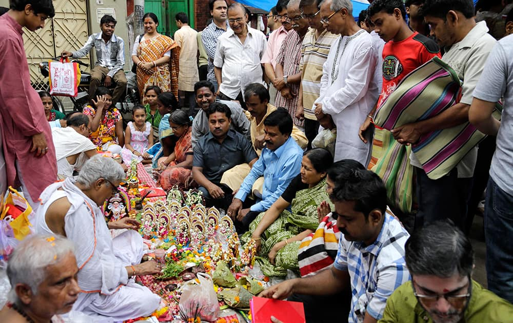 Devotees surround Hindu priests with deities of Ganesha, the elephant-headed God, and Goddess of wealth Laxmi to perform rituals to mark Bengali New Year in Kolkata.
