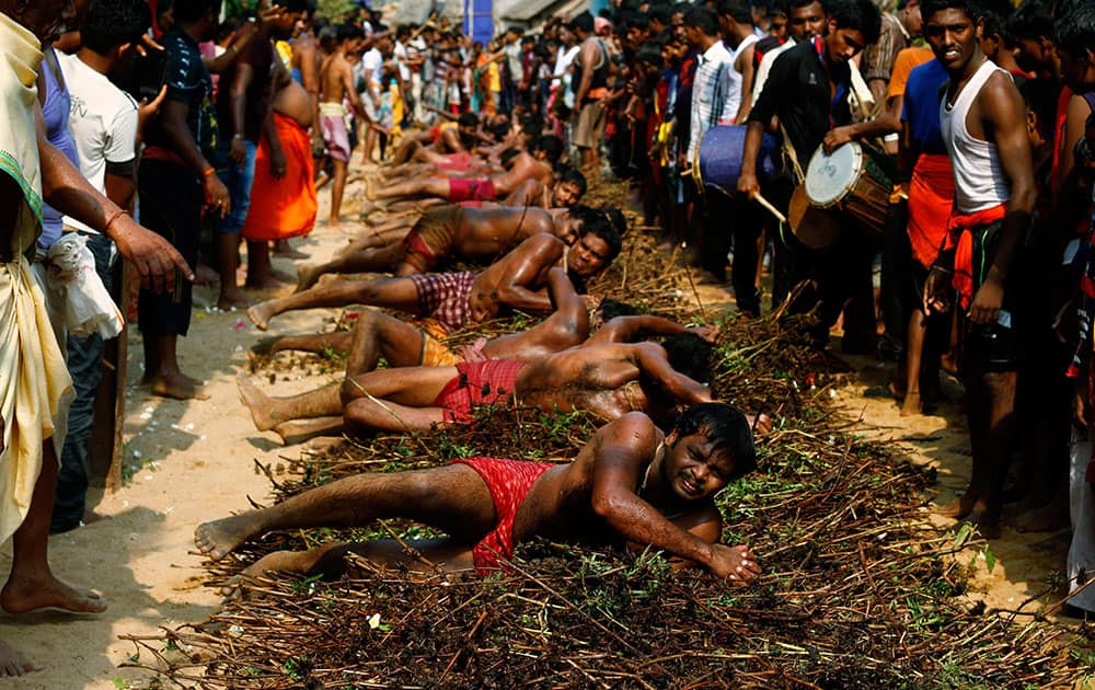 Indian villagers roll on wild thorns placed on road to punish themselves as part of a ritual during the annual Danda festival or the festival of self punishment in Khurda village some 15 miles from the eastern Indian city Bhubaneswar.