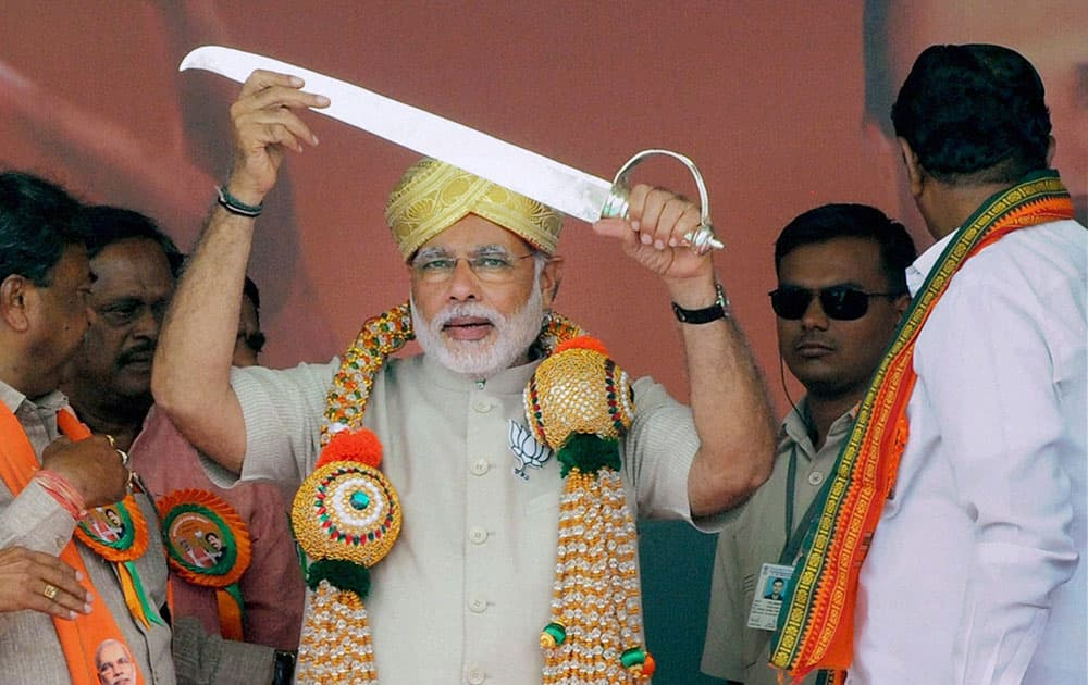 BJP PRIME MINISTER CANDIDATE NARENDRA MODI BEING PRESENTED A SWORD AT A PUBLIC RALLY TO CAMPAIGN FOR BJP CANDIDATE B N BACHEGOWDA AT CHIKKABALLAPUR NEAR BENGALURU.