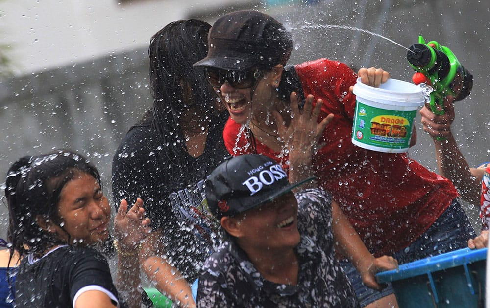 Peoples on a truck react upon being splashed water while others shoot back water guns during during traditional Thai New Year celebrations or Songkran festival in Bangkok.