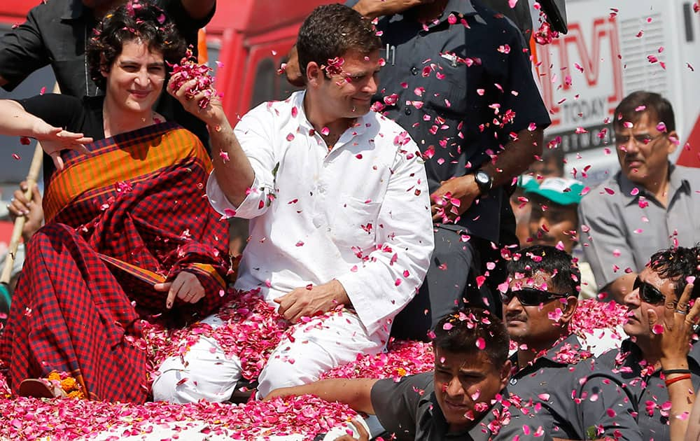 Vice President of India's ruling Congress party Rahul Gandhi, second right, holds a handful of flower petals to throw back at supporters, with his sister Priyanka Vadra seated by his side as he arrives to file his nomination for the ongoing general elections in Amethi, in the northern Indian state of Uttar Pradesh.