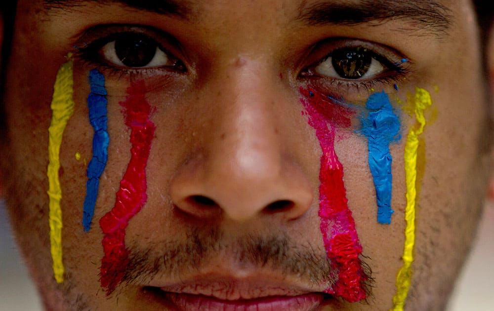 A university student wearing painted tears in the colors of Venezuela`s flag looks into the camera during an anti-government protest in Caracas, Venezuela.