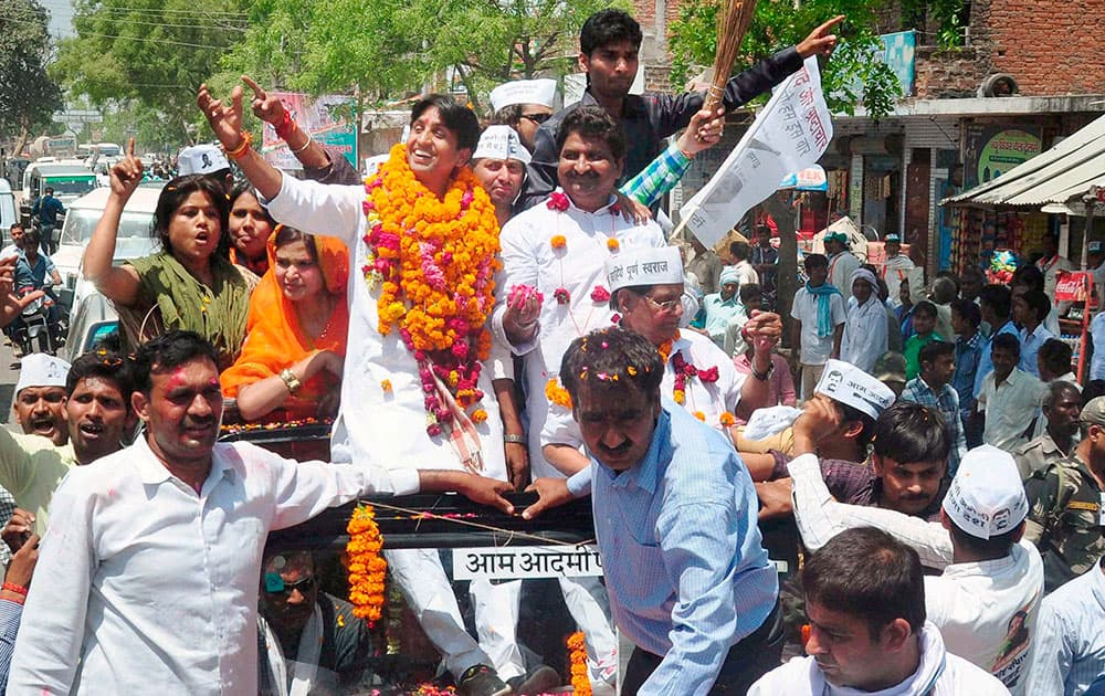 AAP candidate from Amethi Kumar Vishwas waves to supporters on the way to file his nomination papers for Amethi parliamentary seat, in Amethi.
