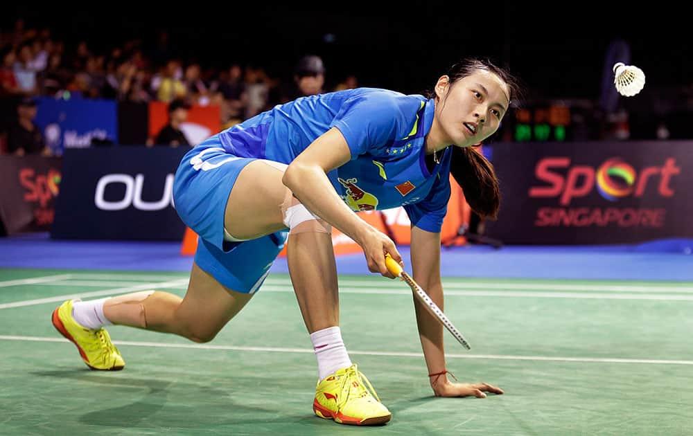 Wang Yihan of China returns a shot to Han Li of China during their semifinal match at the Singapore Open Badminton championship.