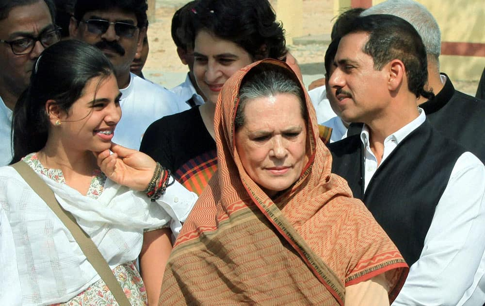 Congress President Sonia Gandhi looks on as her son in law Robert Vadra and dauther Priyanka Vadra admire their daughter Maira (L) after Congress Vice President Rahul Gandhi (unseen) files his nomination papers for Amethi parliamentary seat, in Amethi.