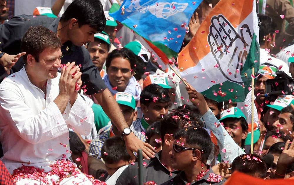 Congress Vice President Rahul Gandhi waves to supporters on the way to file his nomination papers for Amethi parliamentary seat, in Amethi.