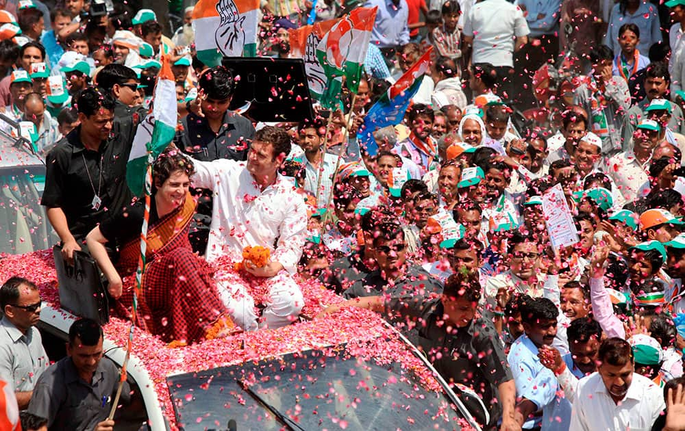 Supporters shower flower petals on Congress Vice President Rahul Gandhi as he along with his sister Priyanka Vadra is on the way to file his nomination papers for Amethi parliamentary seat, in Amethi.