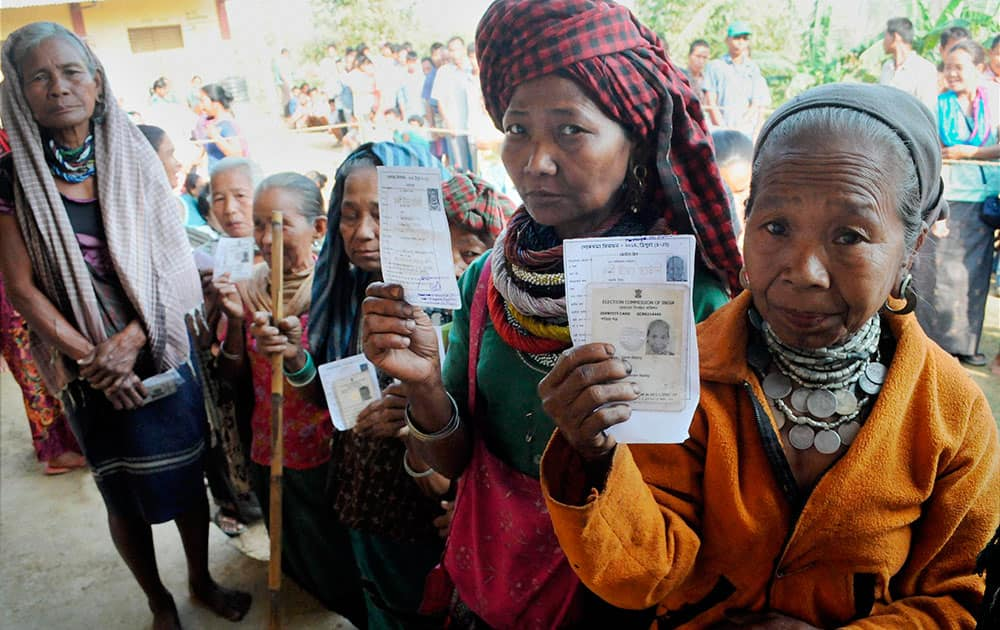 Woman voters show their voter identity cards as they wait in a queue to cast her vote for Tripura West Lok Sabha polls outside a polling station in Dhamcherra.