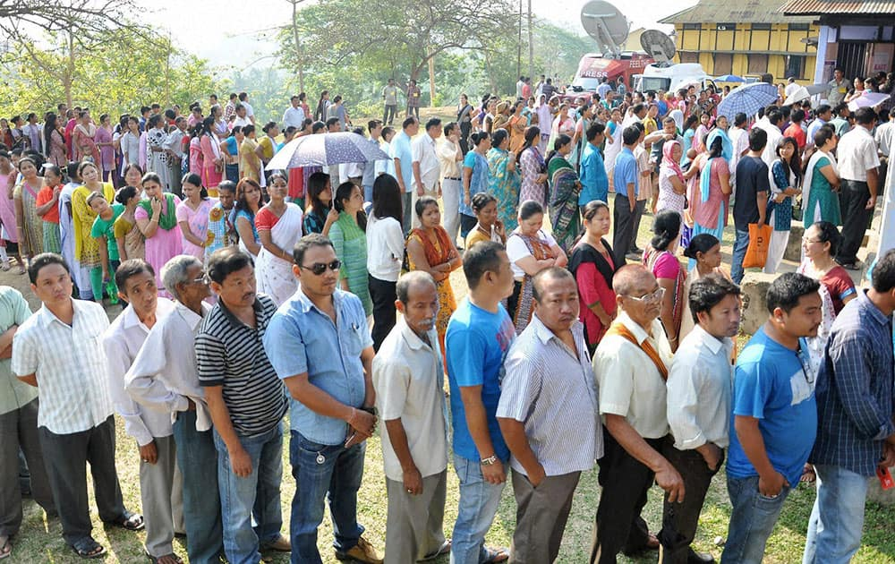 People wait in queues to cast their votes for Lok Sabha polls at a polling station, at Diphu in Karbi Anglong district of Assam.