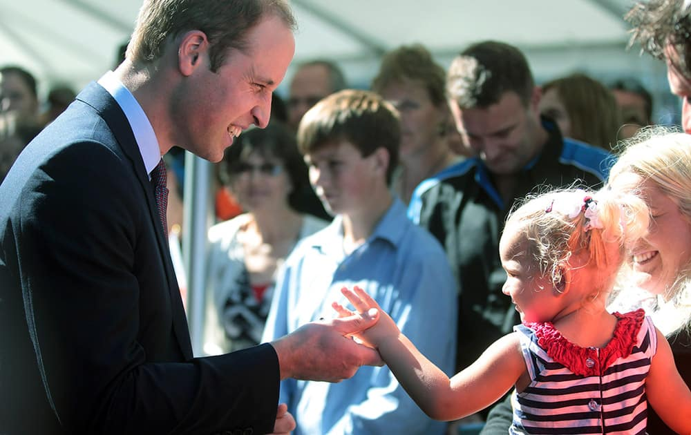 Britain`s Prince William, left, chats with a young girl while visiting aircraft manufacturer Pacific Aerospace near Hamilton, New Zealand.