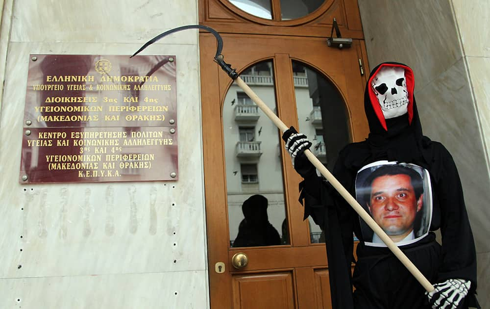 A protester dressed as the grim reaper, and wearing a photo of Health Minister Adonis Georgiadis, stands outside a government health office, in the northern Greek city of Thessaloniki.
