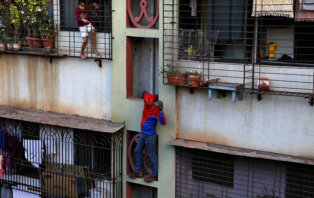 Residents watch as Gaurav Sharma, locally known as Indian Spiderman who is contesting as an independent candidate in the upcoming parliamentary elections climbs a building as part of his campaign in Mumbai.