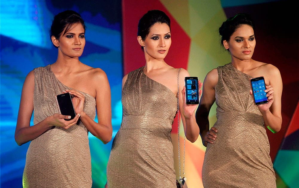 Models display the newly launched Samsung Galaxy S 5 smartphone during a fashion show in Bengaluru.