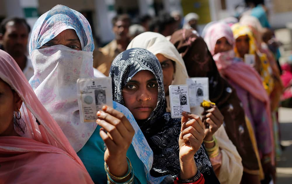 Displaced Muslim riot victims display their voting cards as they wait in line to cast their votes in Kutba village, Muzaffarnagar.