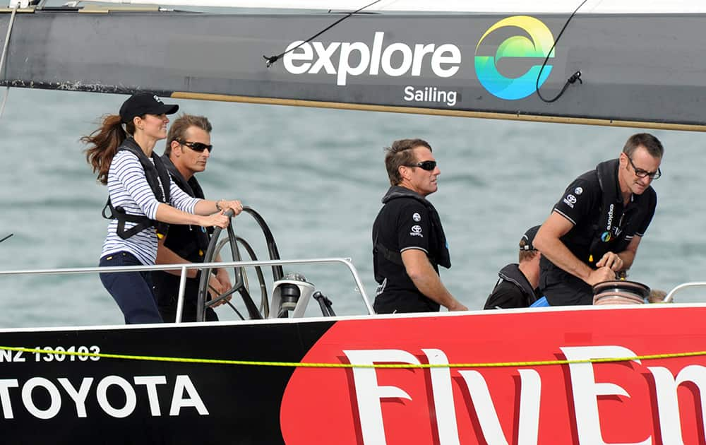 Britain`s Kate, the Duchess of Cambridge stands with New Zealand Americas Cup skipper Dean Barker in a match race against her husband Prince William on the Waitemata Harbour in Auckland, New Zealand.
