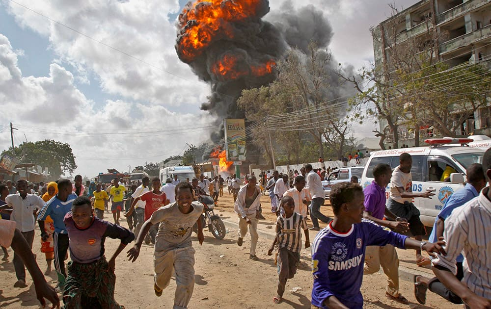 Somalis run from a fireball and explosion during a market fire in the capital Mogadishu, Somalia.