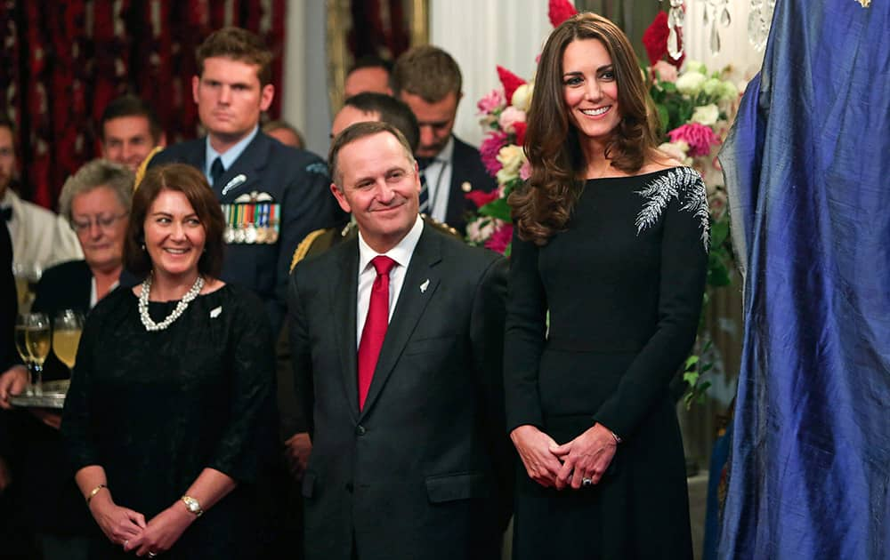 Britain`s Kate, the Duchess of Cambridge, New Zealand`s Prime Minister John Key and his wife Bronagh Key smile during the unveiling of a portrait of Queen Elizabeth II during a state reception at Government House in Wellington, New Zealand.