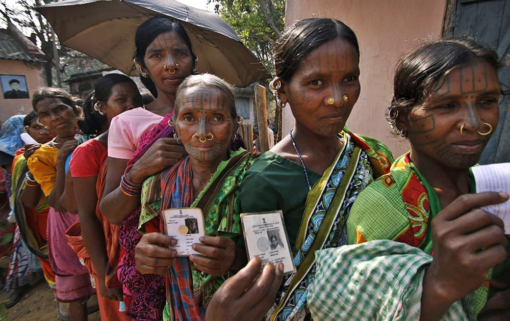 Indigenous women belonging to the Kandha tribe display their voter`s identity cards as they wait to cast their votes outside a polling station during Indian parliamentary elections at Dingesiguda village in Kandhamal district, Odisha.