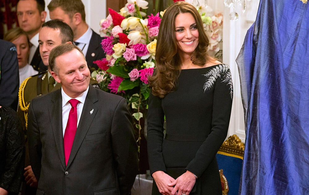 Britain`s Kate, the Duchess of Cambridge, right, and New Zealand`s Prime Minister John Key smile during the unveiling of a portrait of Queen Elizabeth II during a State reception at Government House in Wellington, New Zealand.