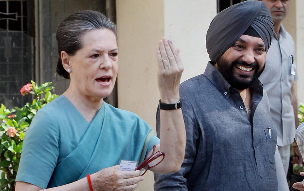 Congress President Sonia Gandhi shows her ink-marked finger after casting vote at Nirman Bhawan polling station in New Delhi during the voting for the third phase of the Lok Sabha elections. DPCC chief Arvinder Singh Lovely is also seen.