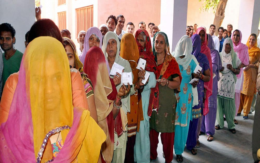 Women show their voting ID card before casting their vote in Sonipat.