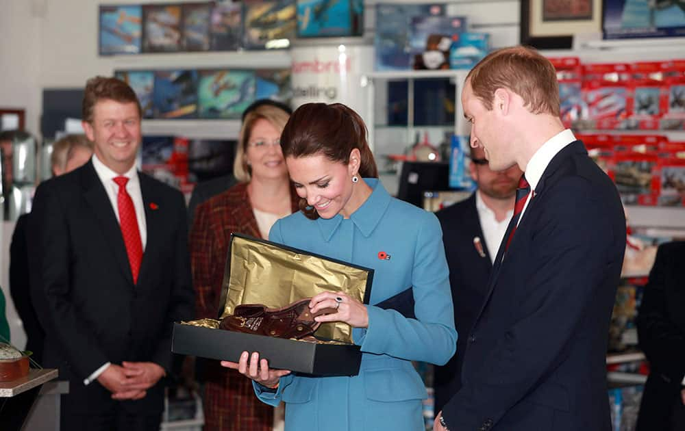 Britain`s Prince William, right, and his wife Kate, the Duchess of Cambridge, center, look at a gift given to them for their son Prince George as they tour the Omaka Aviation Heritage Centre in Blenheim, New Zealand.