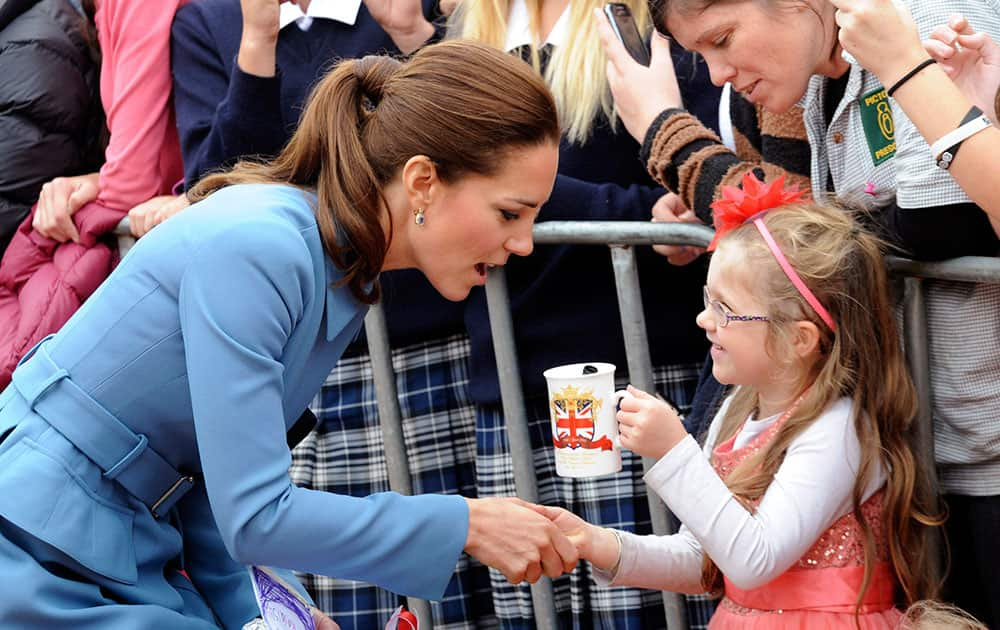 Britain`s Kate, the Duchess of Cambridge, left, chats with a you girl in Seymour Square, Blenhiem, New Zealand.