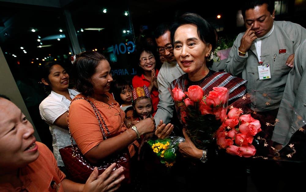 Myanmar Opposition Leader Aung San Suu Kyi, center, arrives at Yangon International Airport to begin her European trip in Yangon, Myanmar.