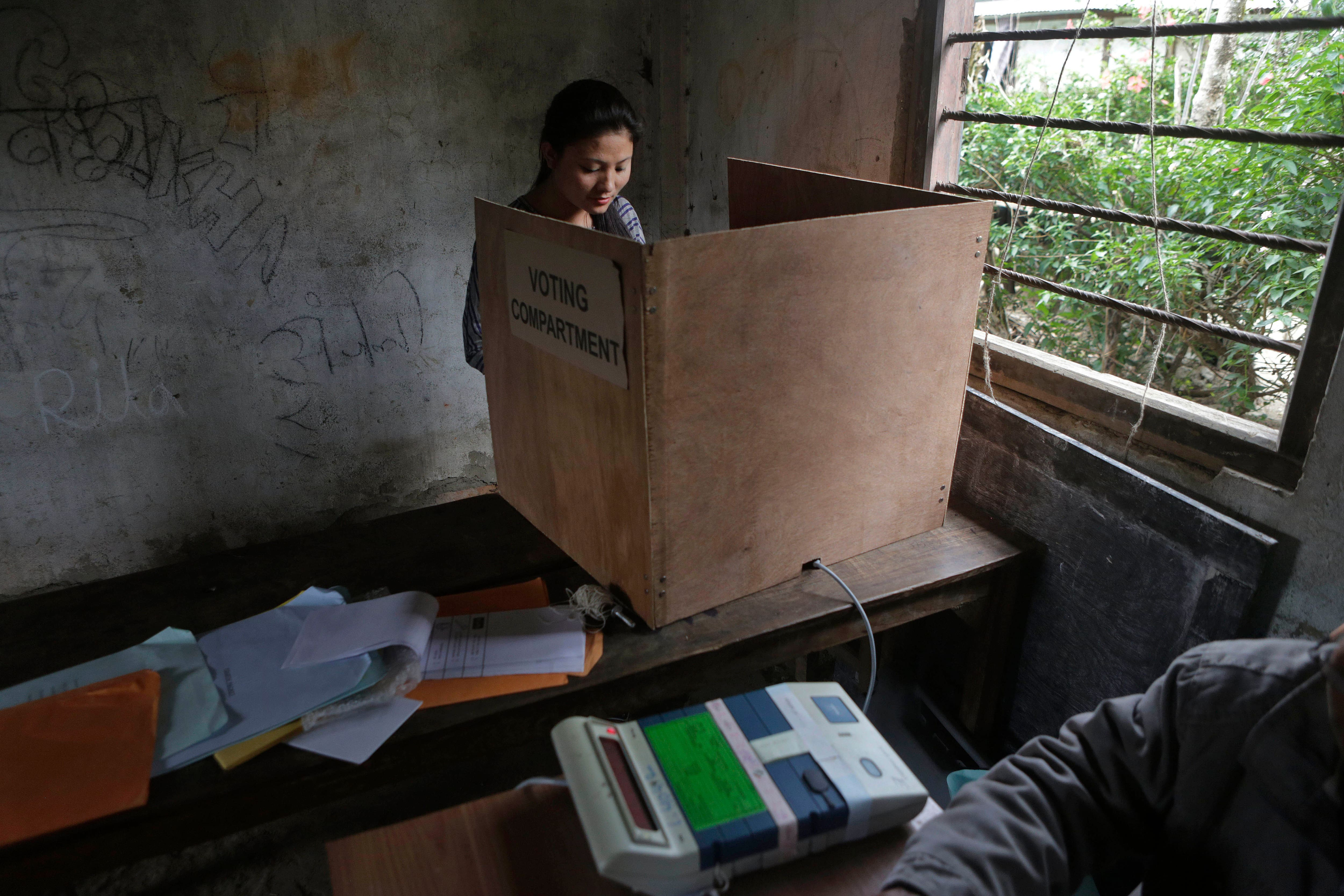 A girl casts her vote at a voting center in Kalapahar, Manipur.