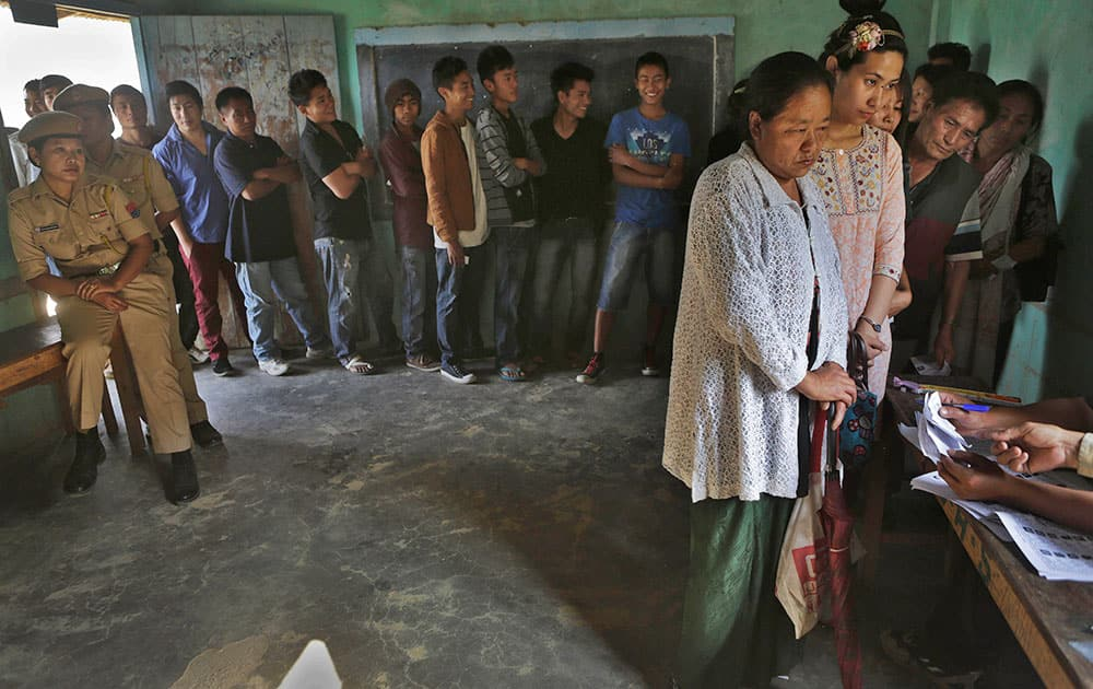 People stand in line to cast their votes inside a voting center at Senapati, in Manipur state.
