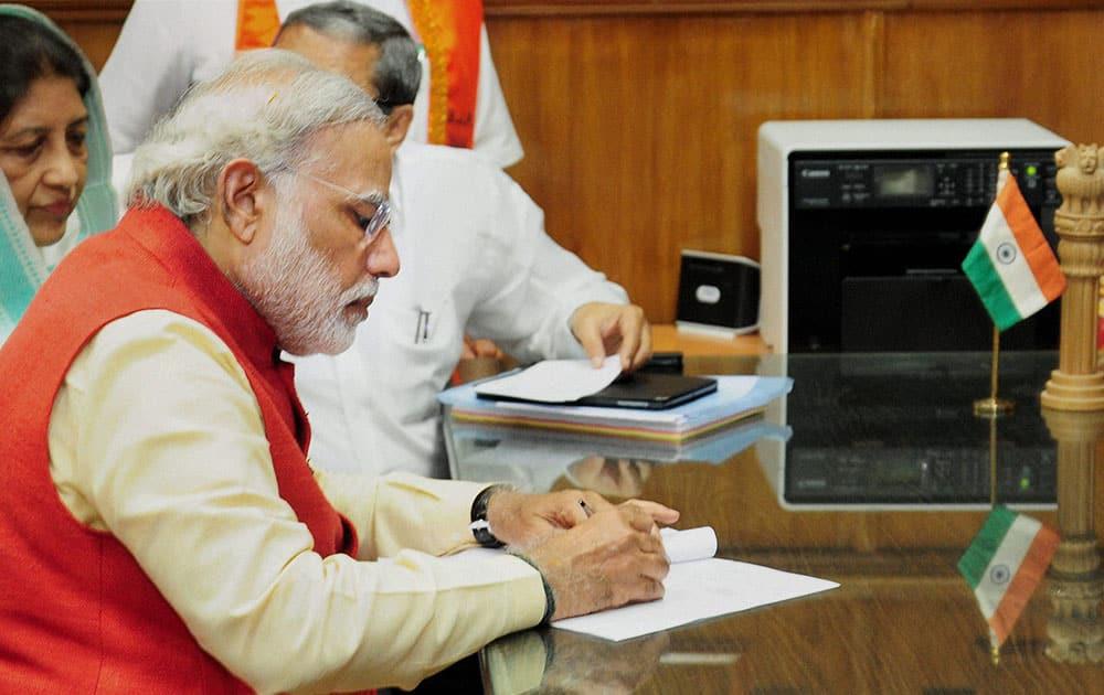 BJP prime Ministerial candidate Narendra Modi signing his nomination form before filing his nominations at Baroda.