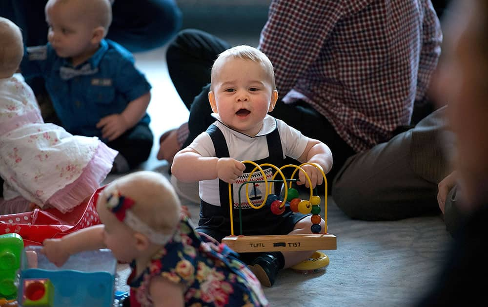Britain`s Prince George, center, plays during a visit to Plunket nurse and parents group at Government House in Wellington, New Zealand.