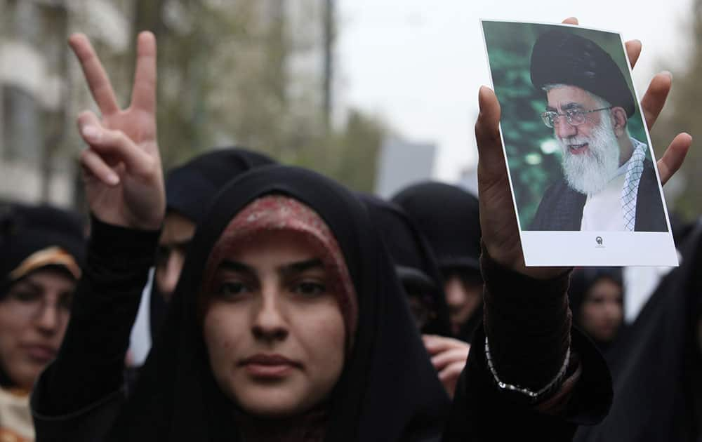 An Iranian woman holds a poster of supreme leader Ayatollah Ali Khamenei during a demonstration of hard-line university students protesting a human rights resolution passed by the European Parliament, in front of the Greek Embassy in Tehran, Iran.