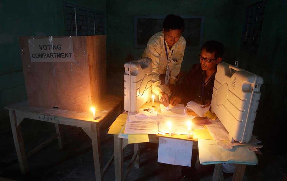 Polling officials check voting materials by candlelight next to electronic voting machines at a voting center on the eve of the second phase of Indian parliamentary elections at Senapati in north eastern Manipur.