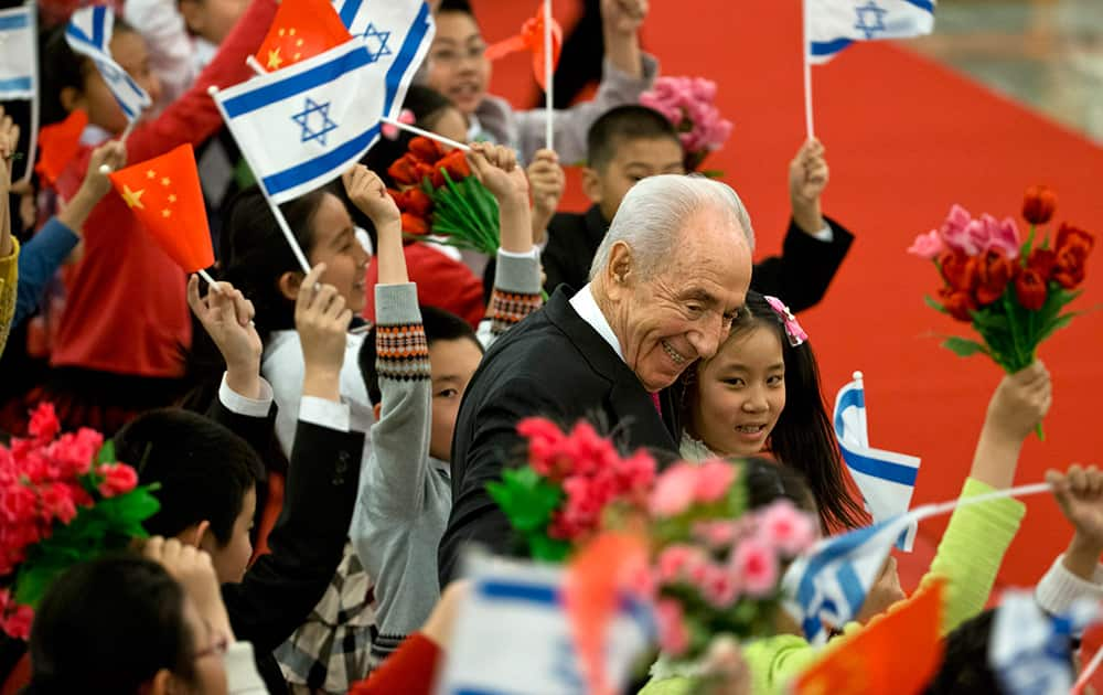 Israeli President Shimon Peres hugs Chinese children during a welcome ceremony held by Chinese president Xi Jinping at the Great Hall of the People in Beijing.