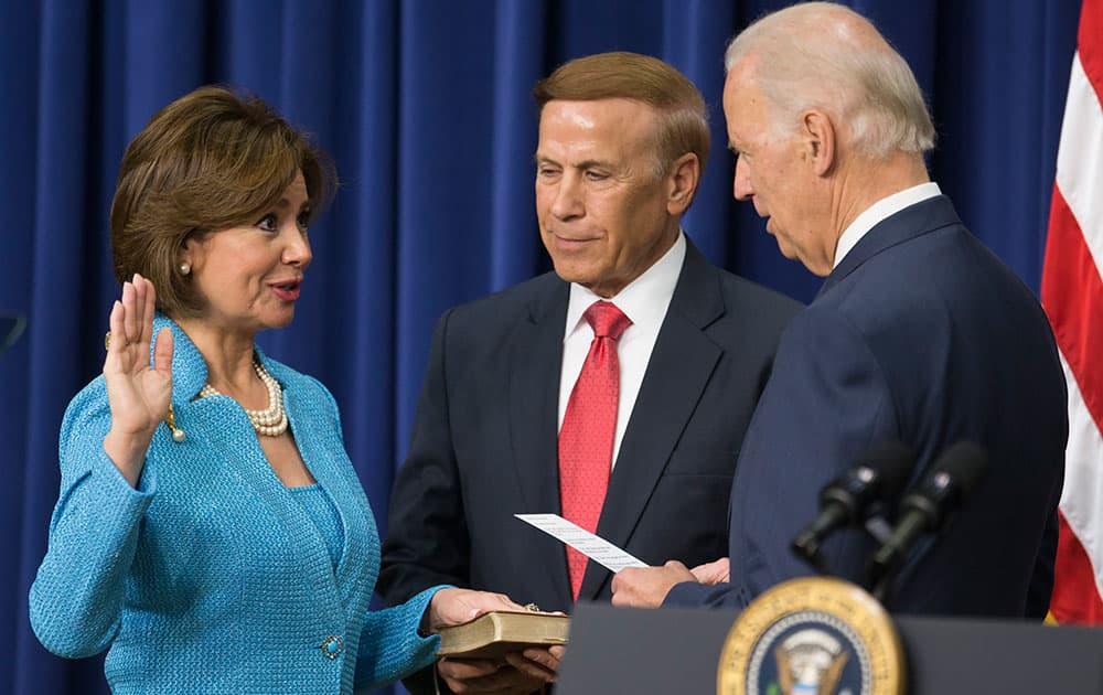 Ray Sweet, center, holds the Bible as his wife Maria Contreras-Sweet, left, takes part in a ceremonial swearing in as administrator of the Small Business Administration with Vice President Joe Biden, in the South Court Auditorium on the White House complex, in Washington.