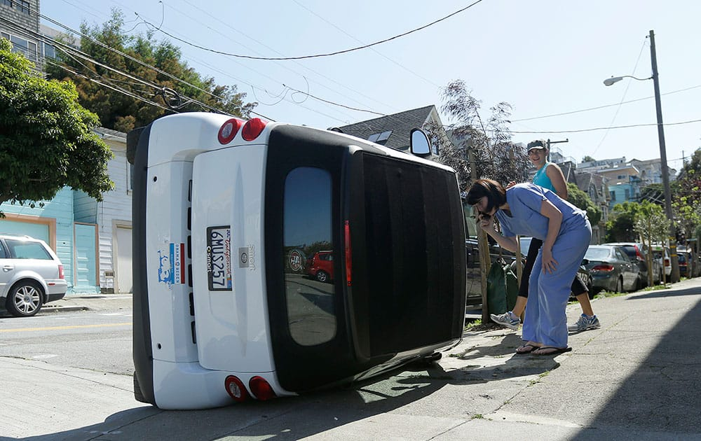 Shelley Gallivan, foreground right, looks into a tipped over Smart car which belongs to her friend on the corner of Prospect and Oso streets in San Francisco.