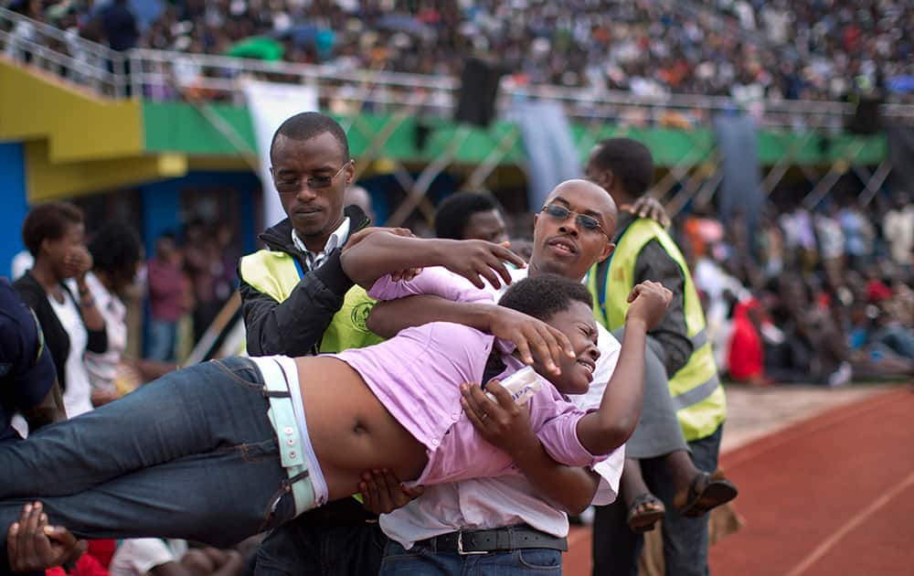 A wailing and distraught Rwandan woman, one of dozens overcome by grief at recalling the horror of the genocide, is carried away to receive help during a public ceremony to mark the 20th anniversary of the Rwandan genocide, at Amahoro stadium in Kigali, Rwanda.