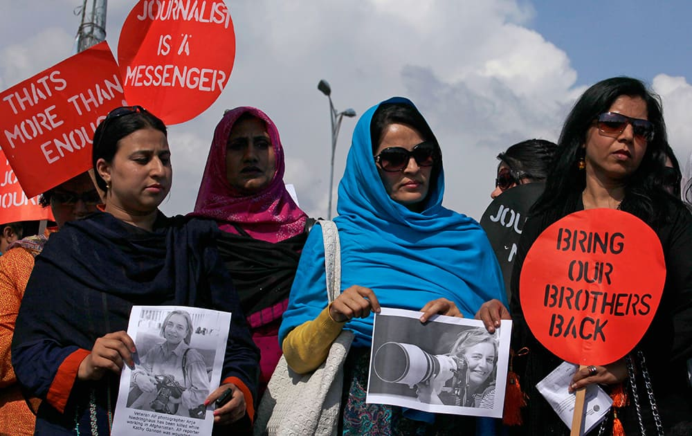 Pakistani journalists hold pictures of Associated Press photographer Anja Niedringhaus, 48, who was killed April 4, 2014 in Afghanistan, during a demonstration in Islamabad, Pakistan.