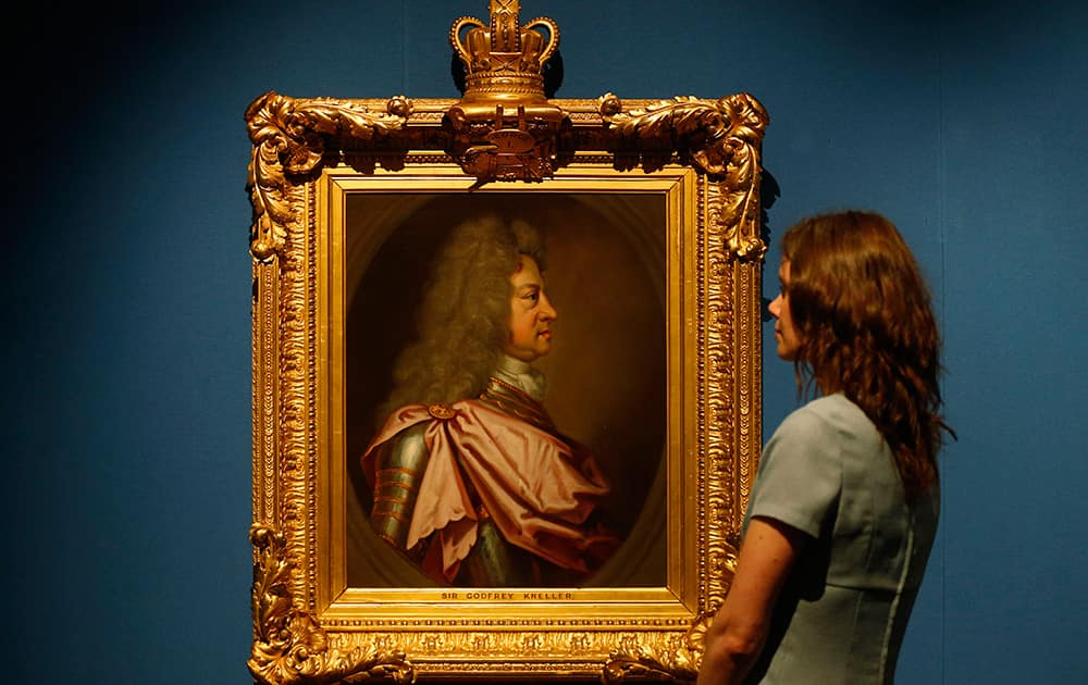 A gallery employee poses with the 1715 painting of King George I by Sir Godfrey Kneller on display in an exhibition `The First Georgians : Art and Monarchy 1714-1760` at The Queen`s Gallery in Buckingham Palace, London.