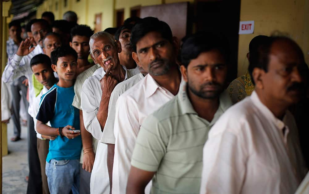 People stand in line to cast their votes during the first phase of elections in Dibrugarh, in the northeastern state of Assam.