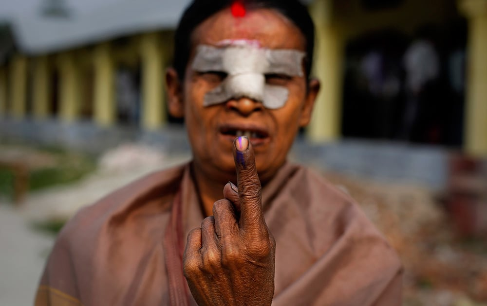 An elderly woman displays her indelible ink mark on her finger after casting her vote outside a polling station during the first phase of elections in Dibrugarh, in the northeastern state of Assam.