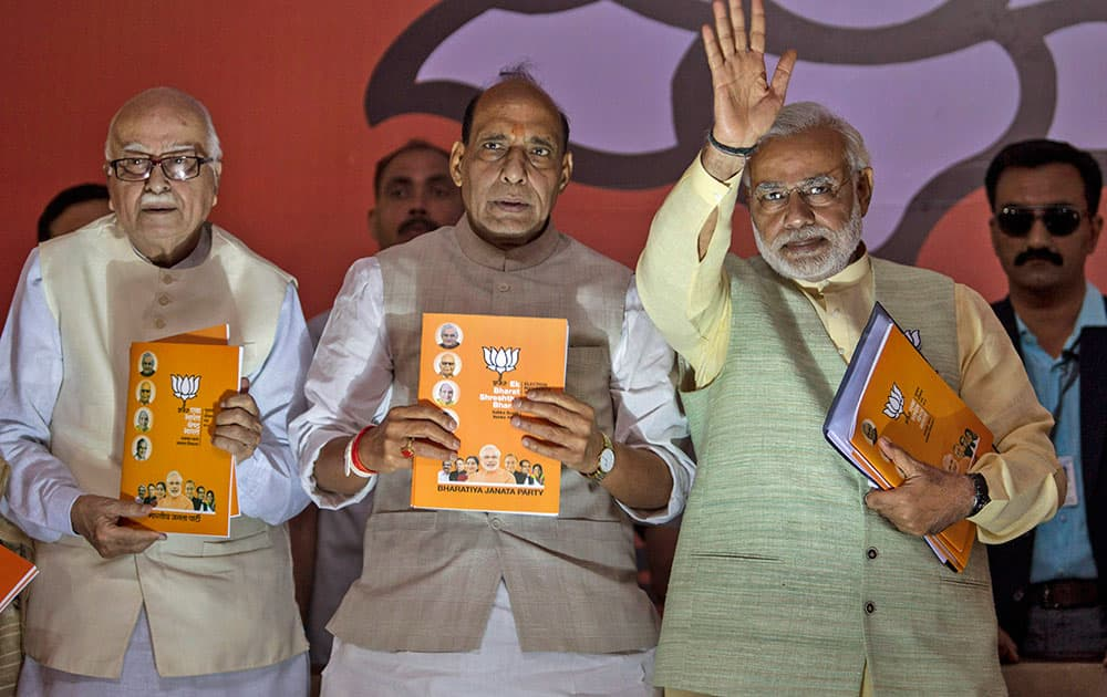 Bharatiya Janata Party (BJP)`s prime ministerial candidate Narendra Modi, right, party president Rajnath Singh, center, and senior leader Lal Krishna Advani release the party manifesto in New Delhi.