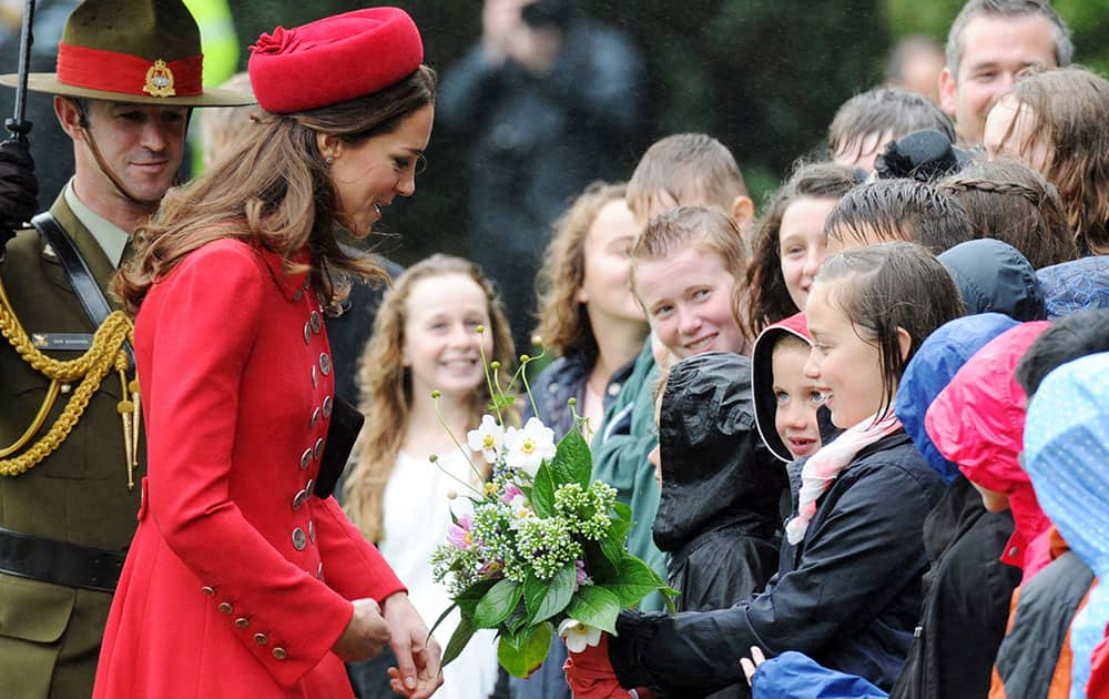 Britain`s Kate, the Duchess of Cambridge receives a bouquet of flowers from school children at the official welcome ceremony at Government House, in Wellington, New Zealand.