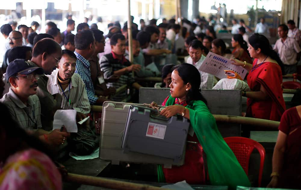 Election officials, left, receive electronic voting machines and other election material at a distribution center set up at a school campus beforeheading to their respective polling stations on the eve of the first phase of national elections in Dibrugarh, in the northeastern Indian state of Assam.