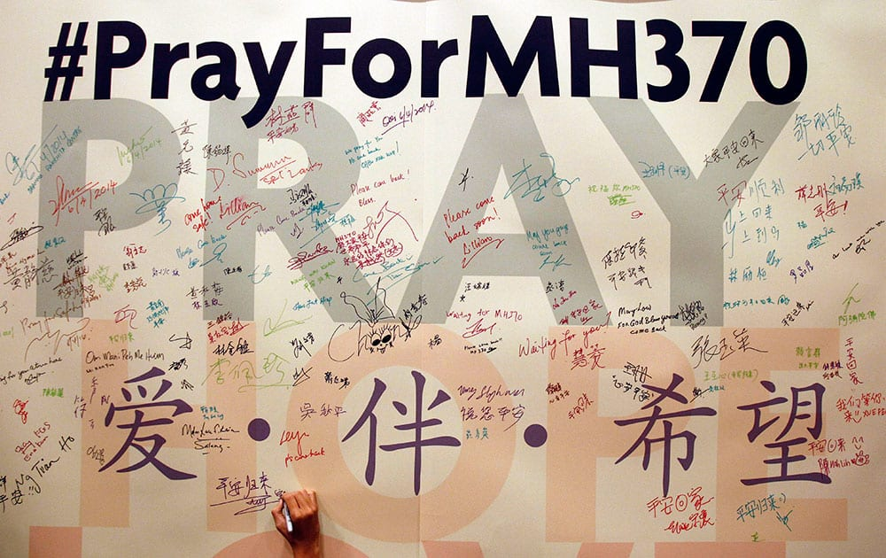 A man writes messages for passengers aboard the missing Malaysia Airlines Flight MH370 before a mass prayer for them, in Kuala Lumpur, Malaysia.