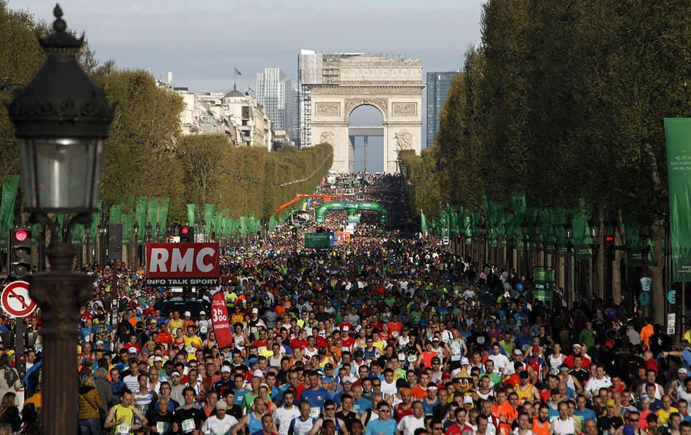 Runners make their way down the Champs Elysees avenue at the start of the 38th Paris Marathon, in Paris.