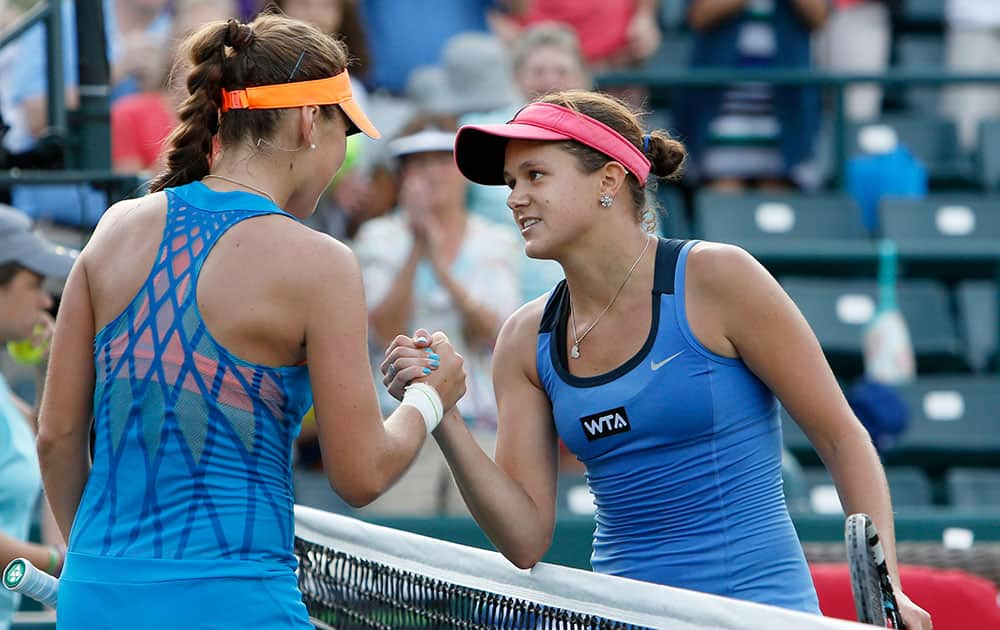 Belinda Bencic, of Switzerland, at left, shakes hands with Jana Cepelova, of slovakia, after a match during the Family Circle Cup tennis tournament in Charleston, S.C.